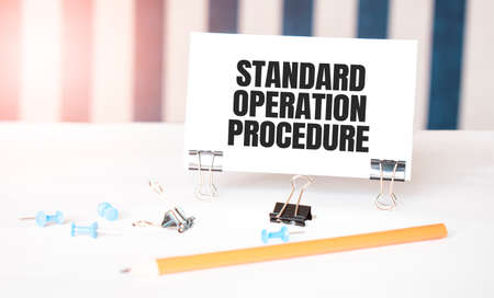 Standard Operation Procedure sign on paper on white desk with office tools. Blue and white background