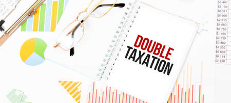 Text DOUBLE TAXATION on white notepad, glasses, graphs and diagrams. Stock Photo