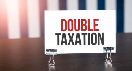 DOUBLE TAXATION sign on paper on dark desk in sunlight. Blue and white background