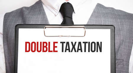 Businessman holding sheet of paper with a message DOUBLE TAXATION