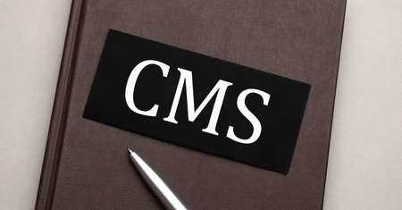 CMS sign written on the black sticker on the brown notepad. Tax concept