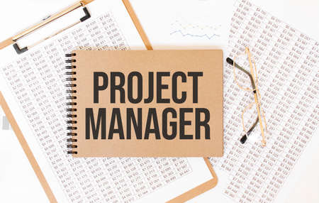 Text PROJECT MANAGER on brown paper notepad on the table with diagram. Business concept