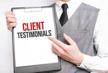 Businessman holding sheet of paper with a message Client Testimonials