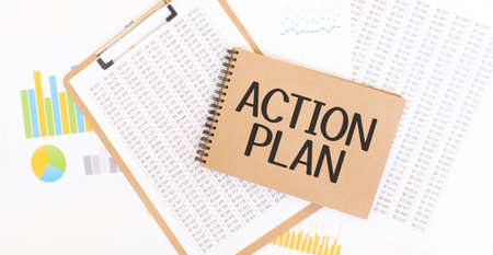 Text ACTION PLAN on brown paper notepad on the table with diagram. Business concept Stock Photo
