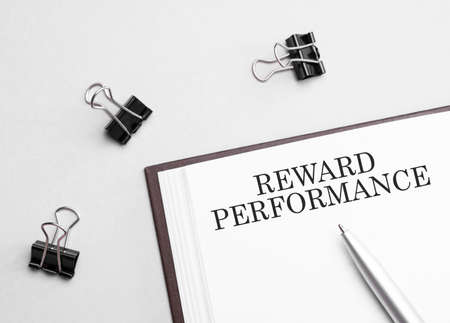 paper note with text REWARD PERFORMANCE, pen and office tools, white background. business concept Banque d'images