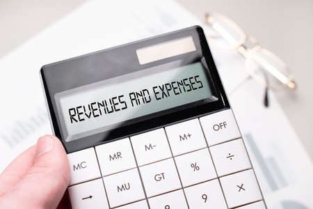 The word REVENUES AND EXPENSES is written on the calculator. Business man holding a calculator in his hand. Stock Photo