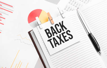 text BACK TAXES on stickers on the diary with office tools