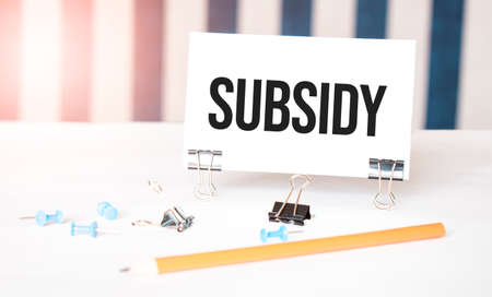 SUBSIDY sign on paper on white desk with office tools. Blue and white background