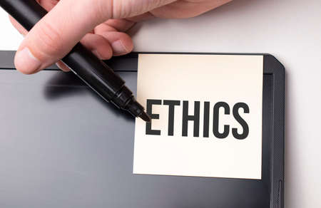 white sticker on the monitor in the office with text ETHICS and hand with marker