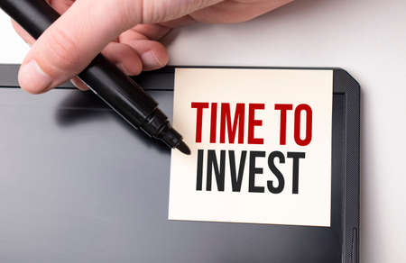 white sticker on the monitor in the office with text Time to invest and hand with marker