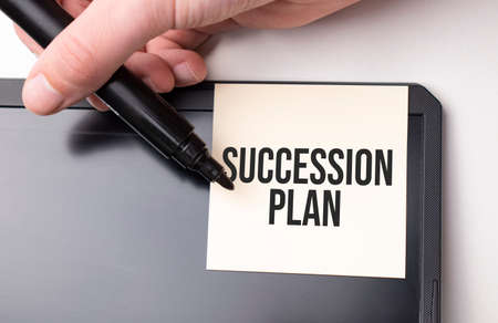 white sticker on the monitor in the office with text SUCCESSION PLAN and hand with marker Standard-Bild