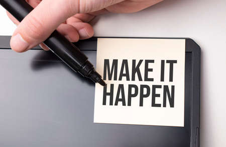 white sticker on the monitor in the office with text Make it happen and hand with marker