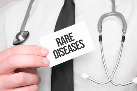 Doctor holding a card with text RARE DISEASES, medical concept