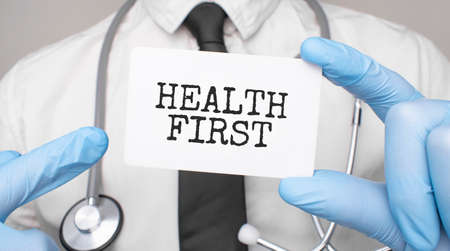 Doctor holding a card with HEALTH FIRST, Medical concept Stock fotó