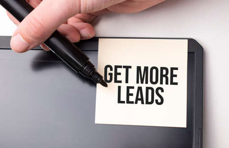 white sticker on the monitor in the office with text Get More Leads and hand with marker