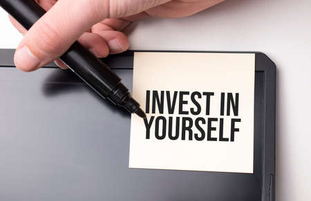 white sticker on the monitor in the office with text Invest in Yourself and hand with marker Standard-Bild