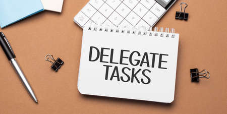 delegate tasks on notepad with pen, glasses and calculator