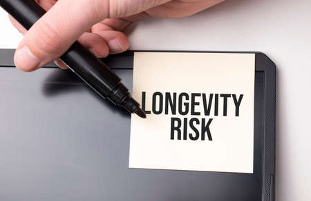 white sticker on the monitor in the office with text LONGEVITY RISK and hand with marker Standard-Bild