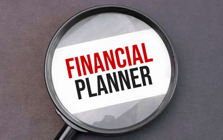 FINANCIAL PLANNER word on paper through magnifying lens. Stock Photo