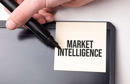 white sticker on the monitor in the office with text Market Intelligence and hand with marker