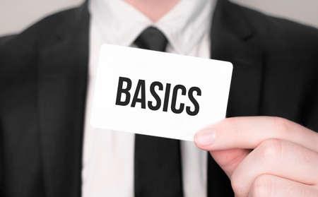Businessman holding a card with text basics