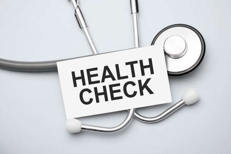 Paper with health check on a table and gray stethoscope