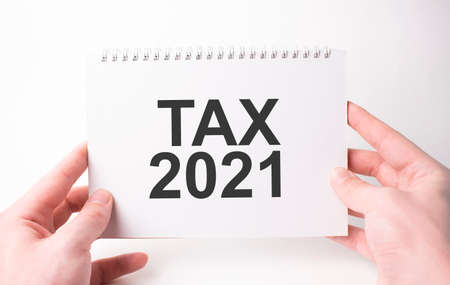 tax 2021 word inscription on white card paper sheet in hands of a man. Black letters on white paper. Business concept. Stok Fotoğraf