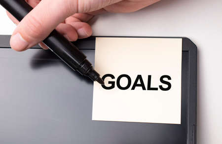 white sticker on the monitor in the office with text goals and hand with marker