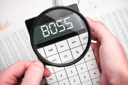 The word boss is written on the calculator. Business man holding a calculator in his hand.