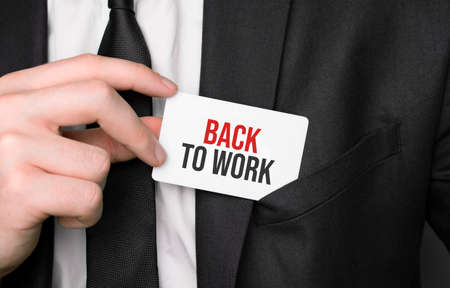 Businessman holding a card with text back to work