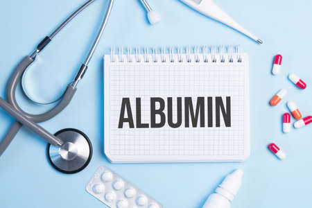 The word albumin written on a white notepad on a blue background near a stethoscope, syringe, electronic thermometer and pills. Medical concept Stok Fotoğraf