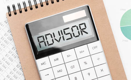 Calculator with text advisor with craft colored notepad pen and financial documents.