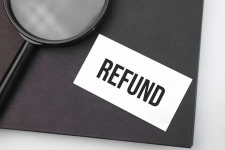 REFUND word on paper and magnifying lens.