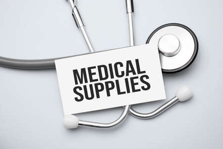 Paper with medical supplies on a table and gray stethoscope