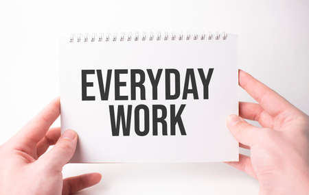 everyday work word inscription on white card paper sheet in hands of a man. Black letters on white paper. Business concept.