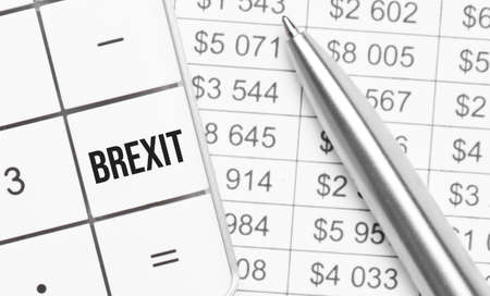 Business and finance. On the table is a report, a pen and a calculator, on the big key of which is written - brexit