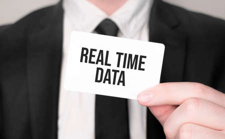Businessman holding a card with text real time data Stok Fotoğraf