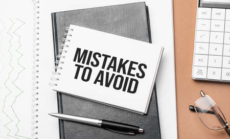 mistakes to avoid on notepad and various business papers on brown background. Brown glasses and magnifier with notepad.