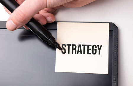white sticker on the monitor in the office with text strategy and hand with marker