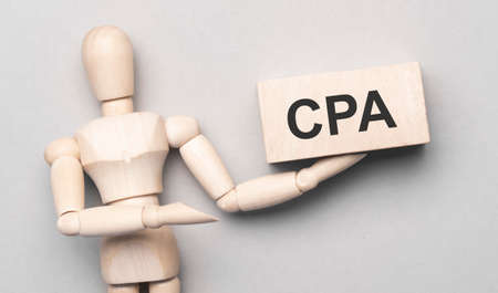 Wooden man shows with a hand to white board with text cpa, concept
