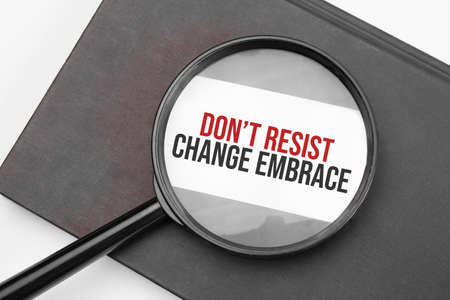 Dont resist change embrace word on paper through magnifying lens.