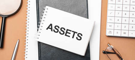 assets on notepad and various business papers on brown background. Brown glasses and magnifier with notepad.