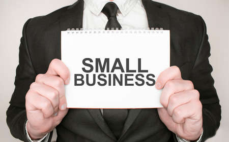 Businessman holding a notepad with text small business