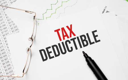TAX DEDUCTIBLE. Conceptual background with chart, papers, pen and glasses