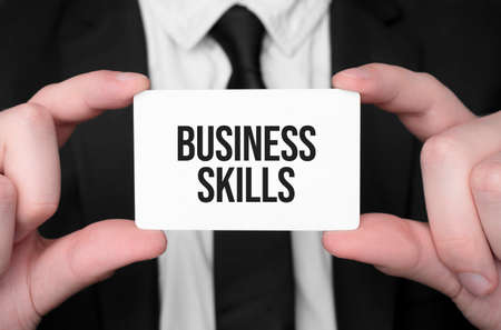 Businessman holding a card with text business skills Stok Fotoğraf