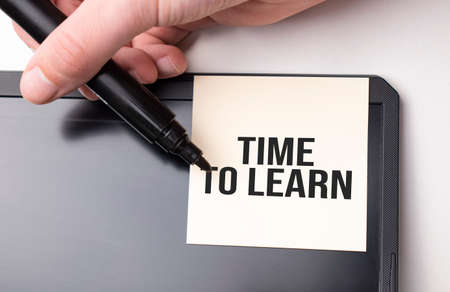 white sticker on the monitor in the office with text Time to Learn and hand with marker