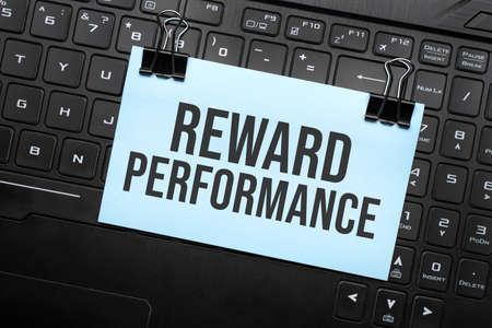 REWARD PERFORMANCE inscription on white paper note on laptop keyboard. Closeup message.