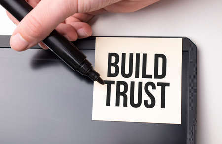 white sticker on the monitor in the office with text BUILD TRUST and hand with marker