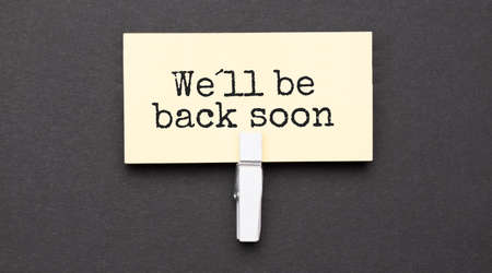 We ll be back soon text on paper with wihte clip. On black background Stock fotó