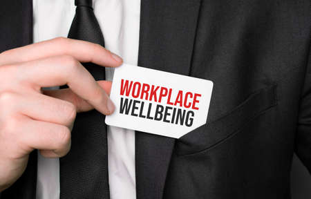 Businessman holding a card with text Workplace Wellbeing